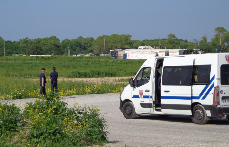 Police outside migrant camp